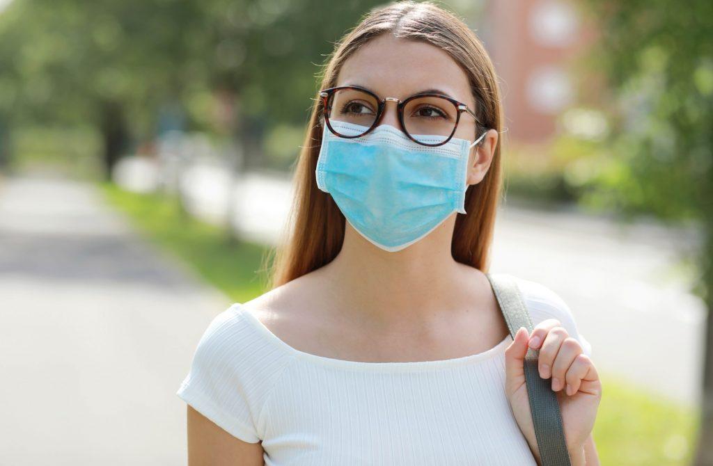 o femeie merge pe strada cu masca pe fata.