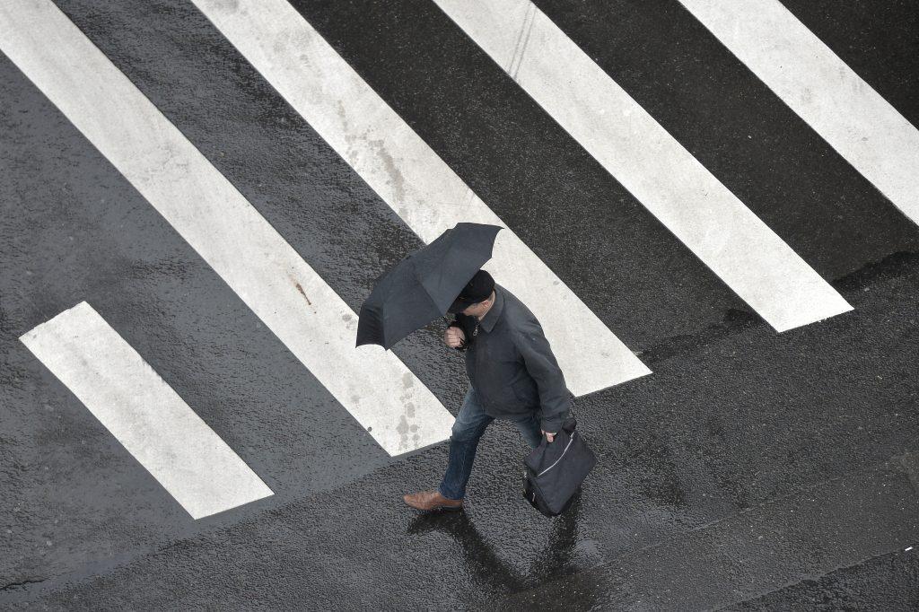 Un bărbat care traversează strada în timp ce ține o umbrelă.